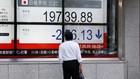 Một người đàn ông nhìn bảng điện tử bên ngoài công ty chứng khoán ở Tokyo. Ảnh:Reuters