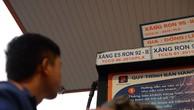 Nhân viên cây xăng tại TP HCM xem bảng giá trước khi bơm xăngcho khách.Ảnh: Hữu Khoa