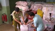 Cán bộ Chi cục quản lý thị trường tỉnh An Giang kiểm tra thuốc lá lậu sau khi thu giữ. Ảnh: BNEWS