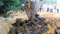 Lực lượng chức năng dùng máy xúc để đào chất thải của Công ty Formosa Hà Tĩnh chôn lấp tại trang trại ông Lê Quang Hòa, tại phường Kỳ Trinh, thị xã Kỳ Anh. Ảnh: TTXVN