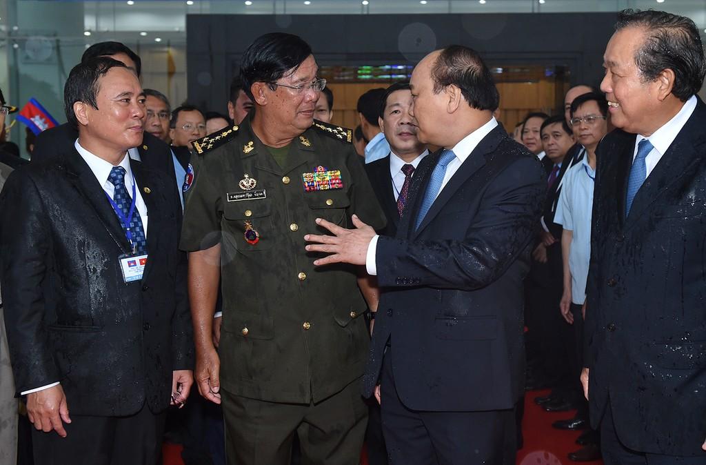 Thủ tướng Nguyễn Xuân Phúc, Phó Thủ tướng Trương Hòa Bình đón Thủ tướng Vương quốc Campuchia Hun Sen trong điều kiện trời mưa khá lớn tại Bình Dương. Ảnh: VGP