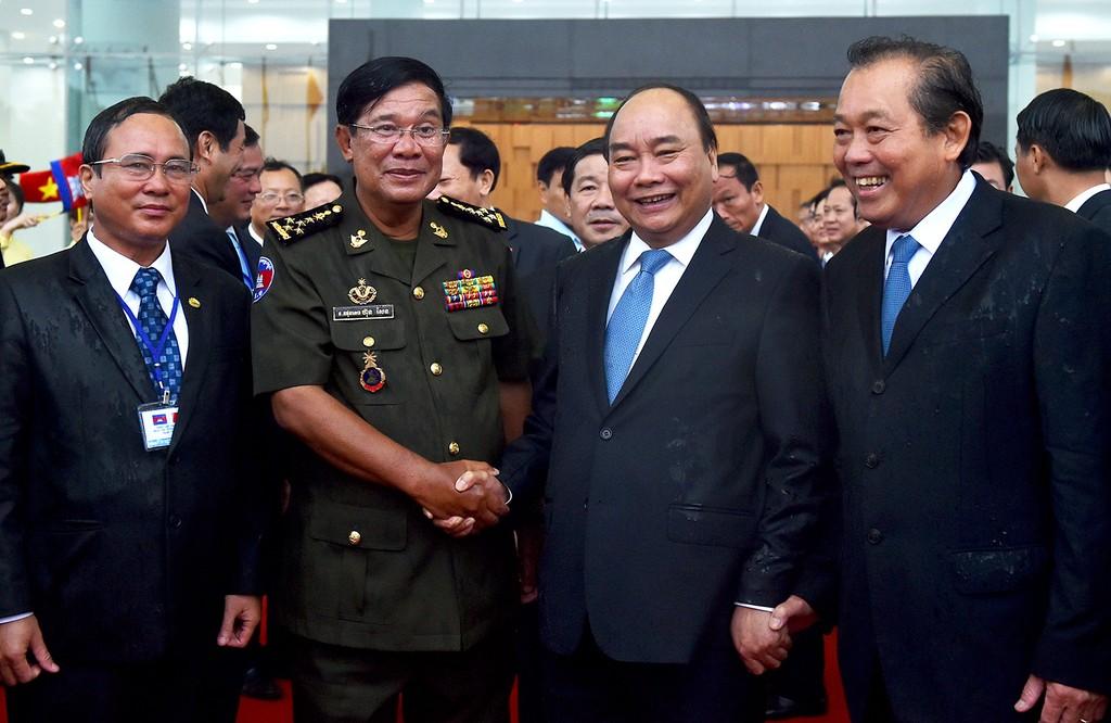 Thủ tướng Nguyễn Xuân Phúc, Phó Thủ tướng Thường trực Chính phủ Trương Hòa Bình đón Thủ tướng Vương quốc Campuchia Hun Sen trong điều kiện trời mưa khá lớn tại Bình Dương. Ảnh: VGP