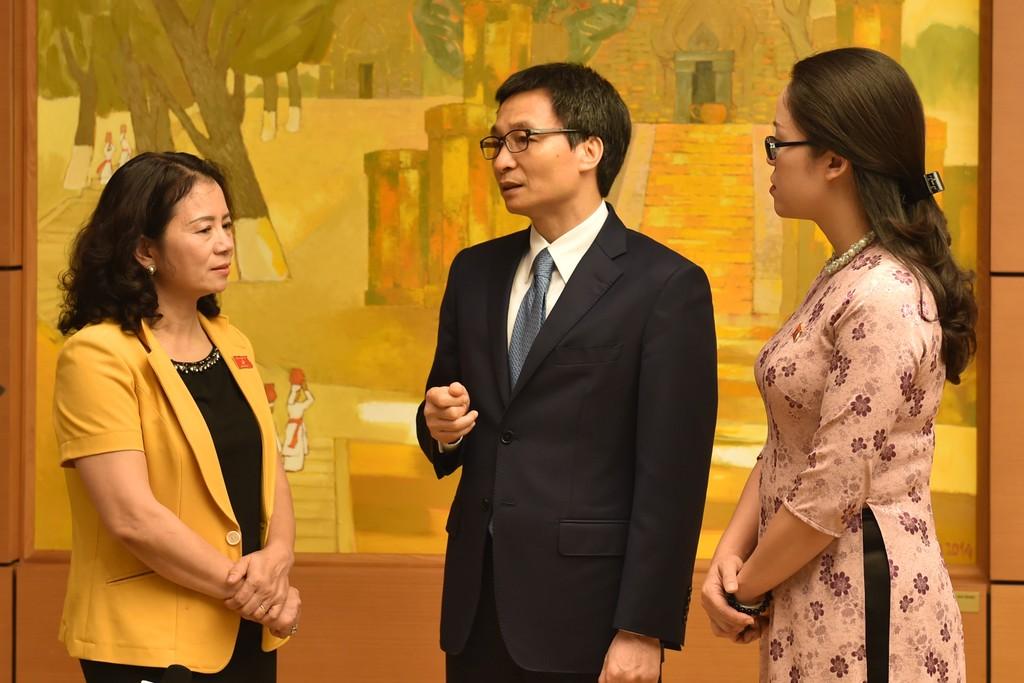 Phó Thủ tướng Vũ Đức Đam trao đổi với đại biểu Quốc hội về vấn đề bỏ biên chế giáo viên. Ảnh: VGP
