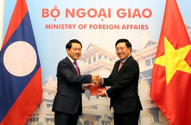 Phó Thủ tướng Phạm Bình Minh và Bộ trưởng Ngoại giao Lào Saleumxay Kommasith trao đổi Nghị định thư về đường biên giới và mốc quốc giới Việt Nam-Lào và Hiệp định về Quy chế quản lý biên giới và cửa khẩu biên giới Việt Nam-Lào. Ảnh: VGP