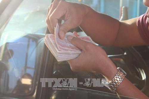 Lái xe tiếp tục sử dụng tiền mệnh giá thấp mua vé tại trạm BOT Biên Hòa - Đồng Nai. Ảnh: TTXVN