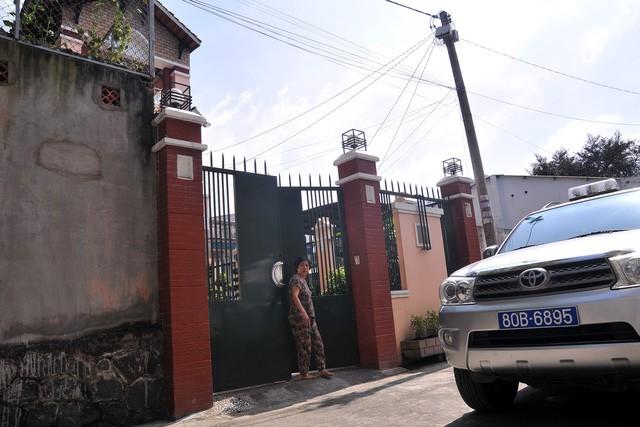 Xe của công an đậu trước nhà riêng của ông Minh để thực hiện khám xét.