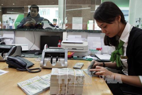 Khách hàng giao dịch tại Hội sở Ngân hàng TMCP Ngoại thương Việt Nam (Vietcombank). Ảnh: TTXVN