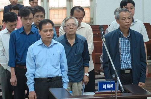 Bị cáo Trung (áo xanh, hàng đầu bên trái) và tám đồng phạm tại tòa.