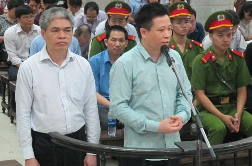 Cựu chủ tịch Hà Văn Thắm (áo xanh) và cựu tổng giám đốc Nguyễn Xuân Sơn trước vành móng ngựa.