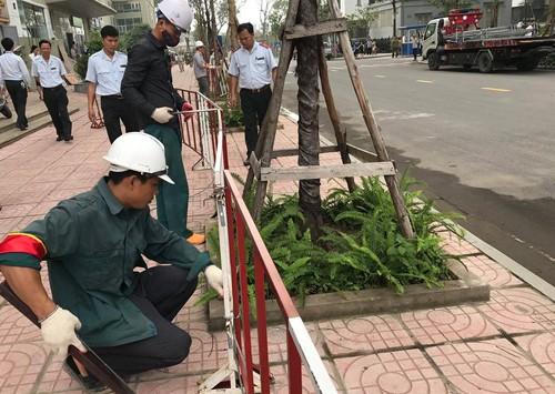 Lực lượng chức năng phá dỡ rào chắn bằng sắt dựng trên vỉa hè chung cư Vinaconex 7.