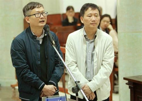 Bị cáo Đinh Mạnh Thắng (áo sẫm màu) và Trịnh Xuân Thanh tại phiên tòa sơ thẩm. Ảnh: TTXVN