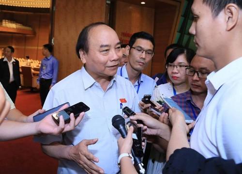 Thủ tướng Nguyễn Xuân Phúc trao đổi với báo chí bên hành lang Quốc hội sáng 7/6. Ảnh: VGP