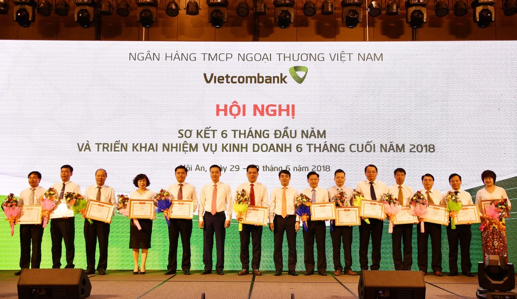 Chủ tịch HĐQT Nghiêm Xuân Thành (thứ 8 từ phải sang) và Tổng giám đốc Phạm Quang Dũng (thứ 6 từ trái sang) tặng Giấy khen và hoa cho 13 chi nhánh tiêu biểu trên một số mặt hoạt động của 6 tháng đầu năm 2018