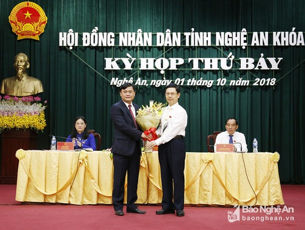 Ông Nguyễn Xuân Sơn - Phó Bí thư Thường trực Tỉnh ủy, Chủ tịch HĐND tỉnh tặng hoa chúc mừng ông Thái Thanh Quý (bên trái)