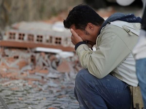 Một người đàn ông ôm mặt khóc bên đống đổ nát tại thị trấn Amatrice. Ảnh:Reuters