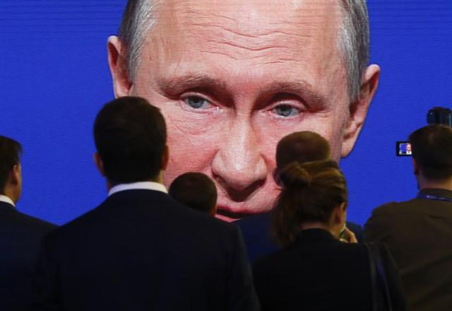 Mọi người theo dõi Tổng thống Nga Vladimir Putin phát biểu tại Diễn đàn Kinh tế Thế giới St. Petersburg tại St. Petersburg, Nga (Ảnh: Sputnik)