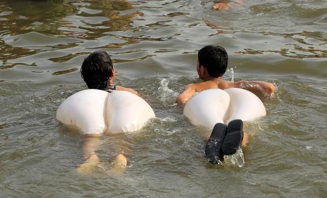 Các cậu bé vui chơi dưới nước để giải nhiệt ngày hè ở Islamabad, Pakistan (Ảnh: Reuters)