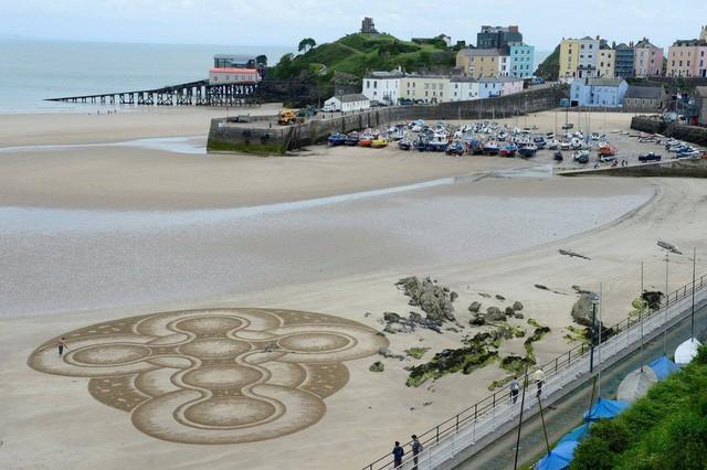 Tác phẩm trên cát ấn tượng nghệ sĩ Marc Treanor tại cảng Tenby, xứ Wales (Ảnh: Reuters)