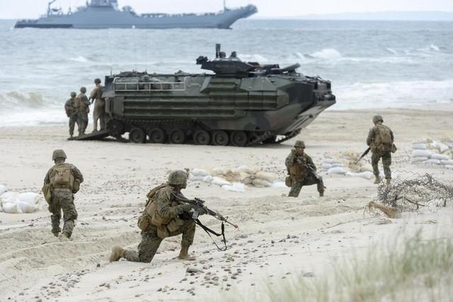 Các binh sĩ phối hợp nhuần nhuyễn với xe quân sự trong một bài tập tấn công đổ bộ (Ảnh: REX)