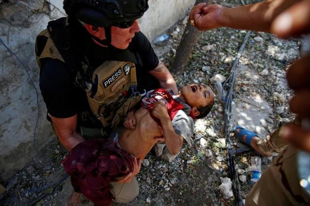 Một binh sĩ Iraq cho một em bé uống nước sau khi cậu bé được giải cứu trong cuộc giao tranh giữa các lực lượng Iraq và các phiến quân Nhà nước Hồi giáo gần thành cổ ở Mosul, Iraq (Ảnh: Reuters)