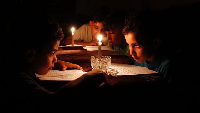 Các em nhỏ đọc sách dưới ánh sáng của nến do thiếu điện tại thành phố Gaza, Palestine (Ảnh: AFP)