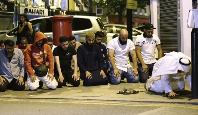 Người dân cầu nguyện tại công viên Finsbury gần một nhà thờ Hồi giáo ở London (Anh), nơi một phương tiện lao vào những người đi bộ trong một vụ tấn công khủng bố (Ảnh: AP)