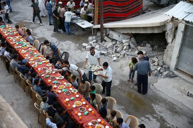 Mọi người tập trung để ăn sáng trong tháng lễ Ramadan giữa các tòa nhà đổ nát tại Damascus, Syria (Ảnh: Reuters)