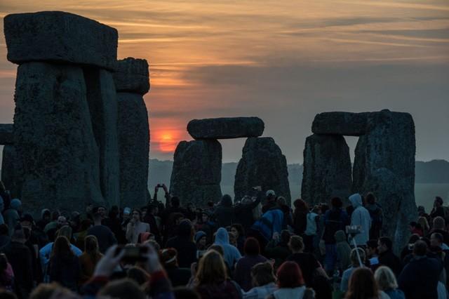 Mọi người ngắm bình minh nhân ngày hạ chí, ngày dài nhất trong năm, tại bãi đá Stonehenge tại Wiltshire, Anh (Ảnh: AP)