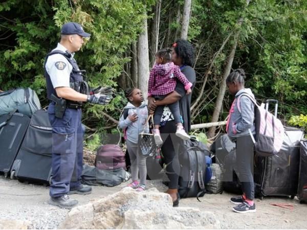Cảnh sát Hoàng gia Canada kiểm tra một gia đình người tị nạn Haiti vào Canada từ Champlain, New York. (Nguồn: Reuters/TTXVN)