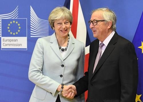 Thủ tướng Anh Theresa May bắt tay Chủ tịch Ùy ban châu Âu Jean-Claude Juncker trong cuộc gặp ngày 8/12 tại Brussels, Bỉ. Ảnh: AFP.