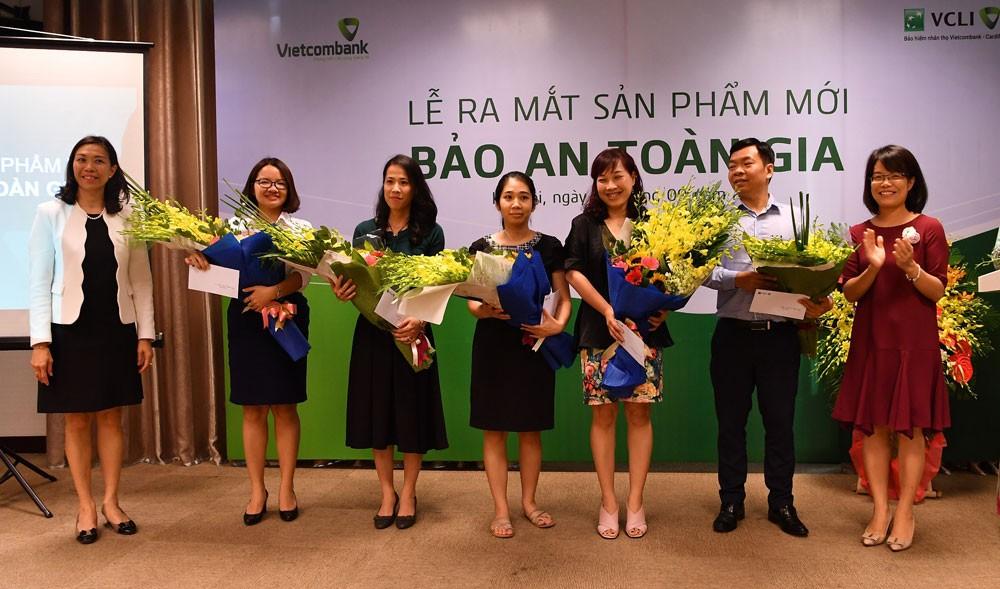 Bà Đoàn Hồng Nhung - Trưởng phòng Quản lý Bán sản phẩm bán lẻ, Thành viên HĐTV Công ty VCLI (thứ 2 từ phải sang) và bà Young Lai Yin - Tổng giám đốc VCLI (ngoài cùng bên trái) tặng hoa chúc mừng các khách hàng tham gia sản phẩm Bảo an Toàn gia