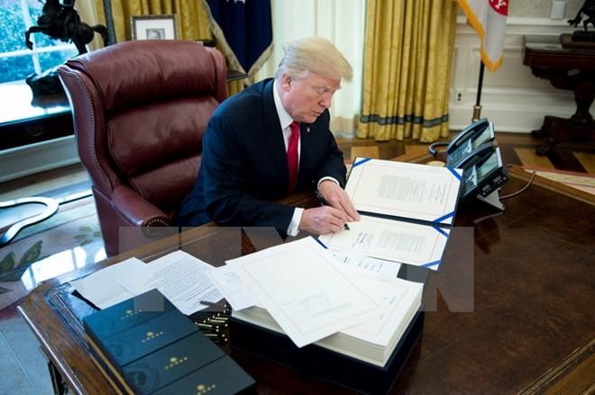 Tổng thống Mỹ Donald Trump ký một văn bản ở Washington DC., ngày 22/12/2017. (Ảnh: AFP/TTXVN)