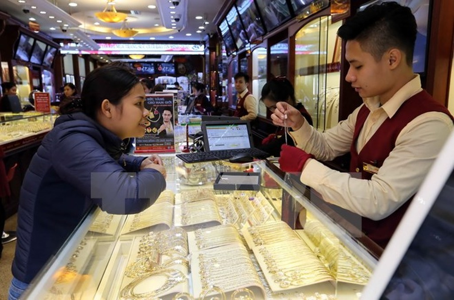 Mua bán vàng tại cửa hàng của Công ty Vàng bạc Bảo Tín Minh Châu, phố Trần Nhân Tông, quận Hai Bà Trưng, Hà Nội. (Ảnh: Trần Việt/TTXVN)