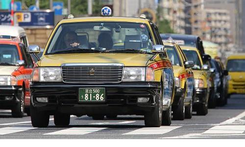 Các xe taxi dừng đèn đỏ trên đường phố Tokyo. Ảnh:Bloomberg.