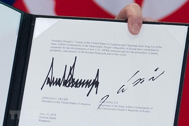 Văn kiện chung lưu lại chữ ký của Tổng thống Mỹ Donald Trump (trái) và của nhà lãnh đạo Triều Tiên Kim Jong-un (phải) tại Sentosa, Singapore ngày 12/6. (Nguồn: AFP/TTXVN)