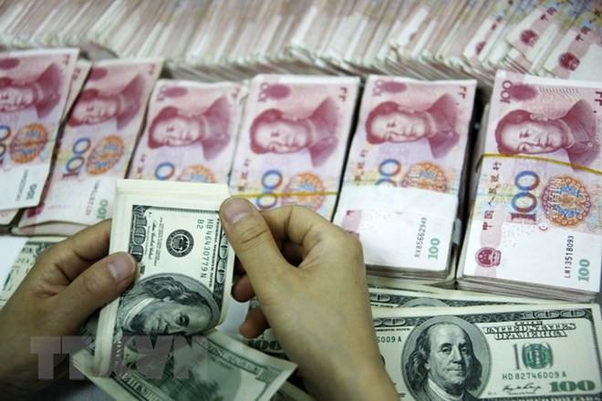 Đồng tiền giấy 100 USD (trên) và đồng 100 nhân dân tệ (phía dưới) tại một ngân hàng ở Hoài Bắc, tỉnh An Huy. (Nguồn: AFP/TTXVN)