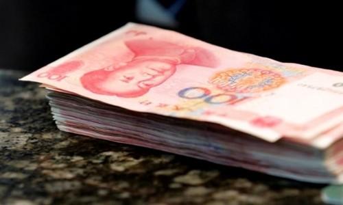 Các tờ 100 NDT trên quầy giao dịch tại một ngân hàng ở Bắc Kinh. Ảnh:Reuters