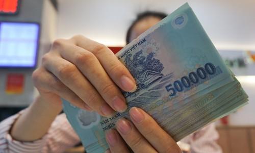 Giao dịch tiền mặttại một ngân hàng ởHà Nội. Ảnh:Anh Tú