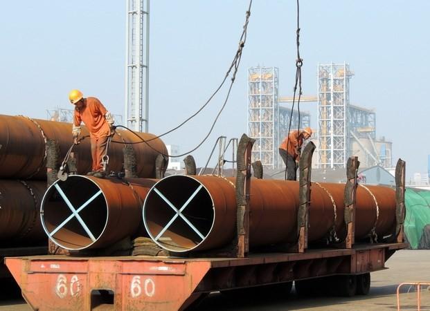 Công nhân vận chuyển thép tại một cảng ở thành phố Liên vận cảng, tỉnh Giang Tô, Trung Quốc. (Nguồn: AFP/TTXVN)