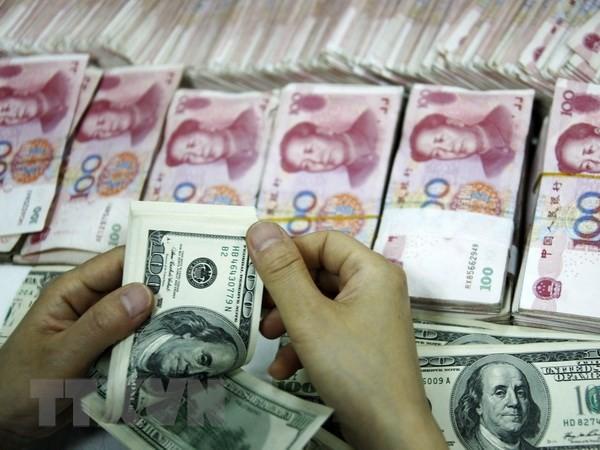 Đồng tiền giấy 100 USD (trên) và đồng 100 Nhân dân tệ (phía dưới) tại một ngân hàng ở Hoài Bắc, tỉnh An Huy, Trung Quốc. (Nguồn: AFP/ TTXVN)