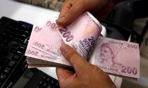 Nhân viên kiểm tiền tại một quầy đổi ngoại tệ ở Istanbul. Ảnh:Reuters