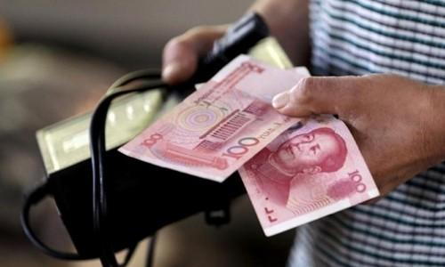 Người mua hàng cầm tờ 100 NDT tại một khu chợ ở Bắc Kinh. Ảnh:Reuters