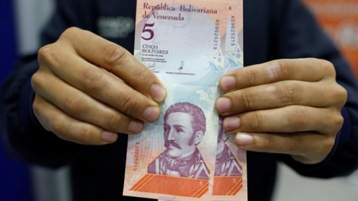 Đồng 5 Bolivar mới được rút ra từ một cây ATM ở Caracas, Venezuela, ngày 20/8 - Ảnh: Reuters.