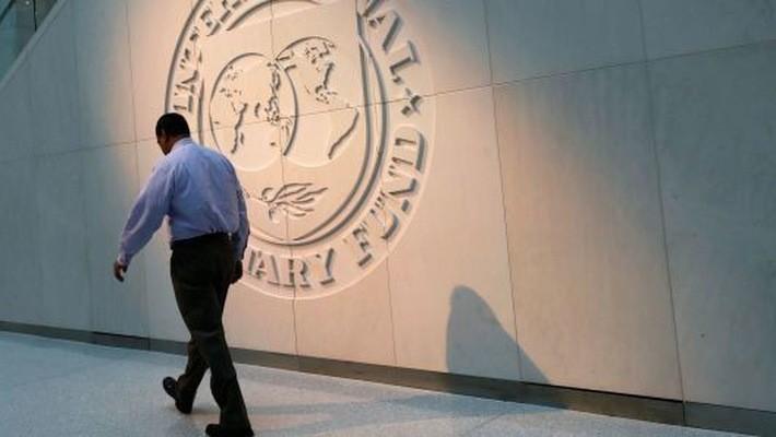 Một người đàn ông đi ngang qua logo của Quỹ Tiền tệ Quốc tế (IMF) bên ngoài trụ sở của định chế này ở Washington DC, Mỹ - Ảnh: Reuters.