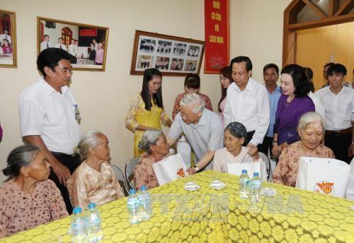 Tổng Bí thư Nguyễn Phú Trọng đến từng phòng ở, thăm hỏi, động viên và tặng quà cho người có công với cách mạng đang điều dưỡng tại Trung tâm. Ảnh: TTXVN