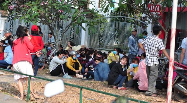 Các công nhân ngồi chờ đợi thông tin phía trước cổng doanh nghiệp