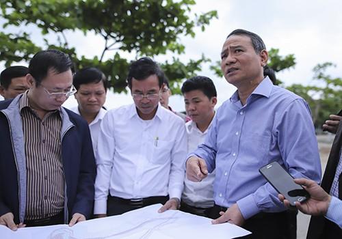 Bí thư Thành ủy Đà Nẵng Trương Quang Nghĩa (bìa phải) xem bản đồ dự án nghỉ dưỡng ở Nam Ô và chỉ đạo tháo gỡ ngay hàng rào chắn sát mép biển.