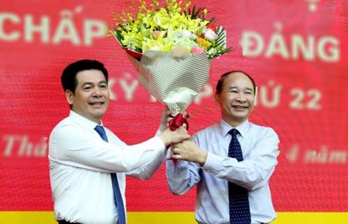 Ông Nguyễn Hồng Diên (trái) nhận hoa chúc mừng từ Bí thư Phạm Văn Sinh (nghỉ hưu từ 1/5).