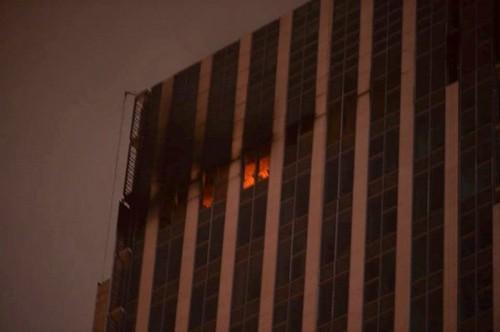Lửa và khói bốc lên từ tầng 25 toà cao ốc trên đường Lê Văn Lương. Ảnh: MXH