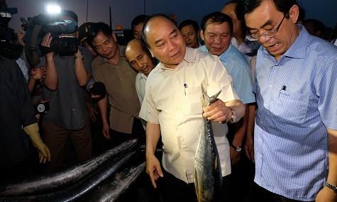 Thủ tướng Nguyễn Xuân Phúc mua cá của ngư dân Quảng Trị - Ảnh: VGP